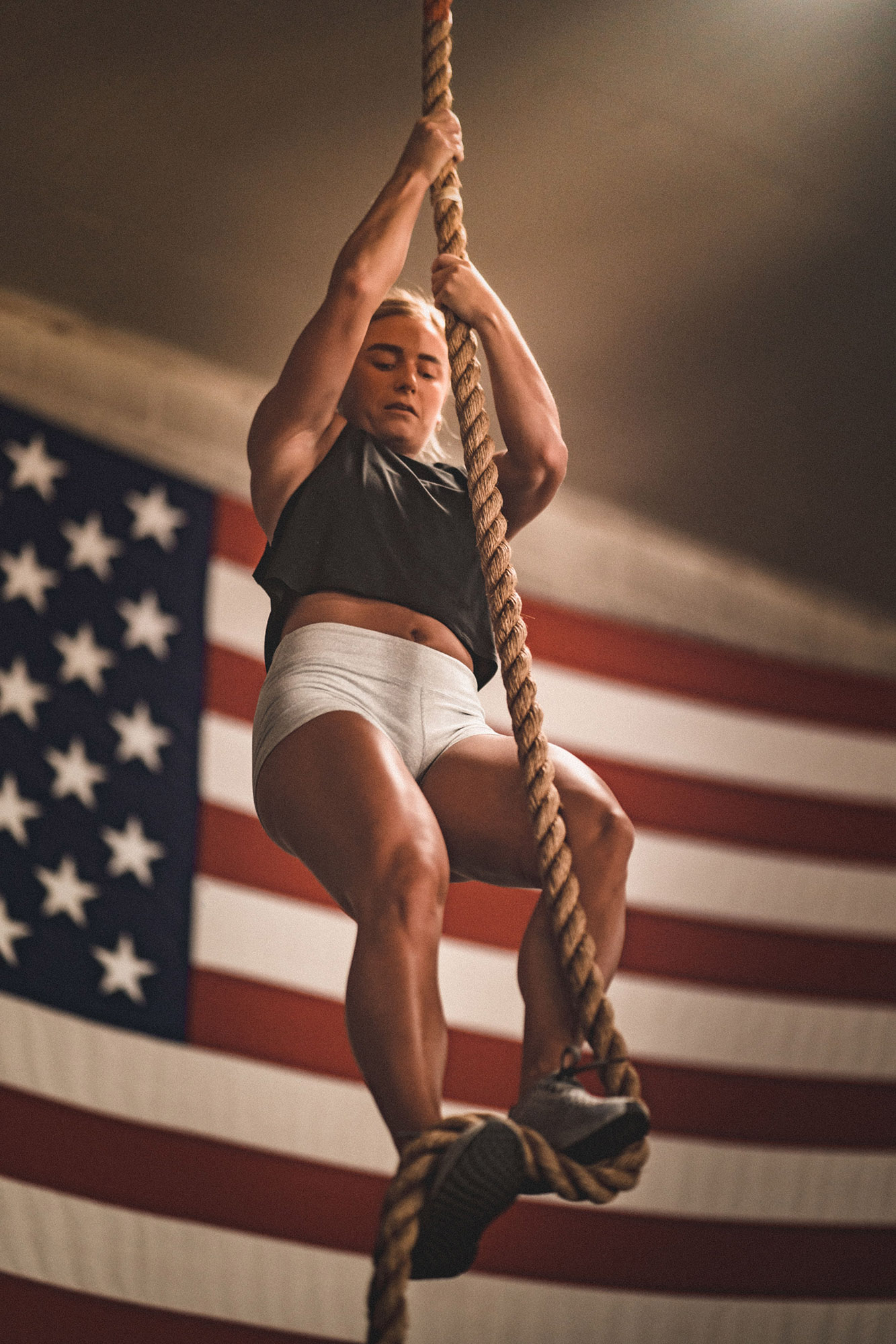 woman climbing rope during a crossfit workout