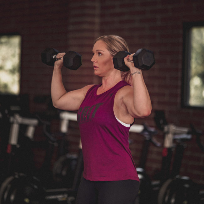 woman with good physique doing a daily workout with weights